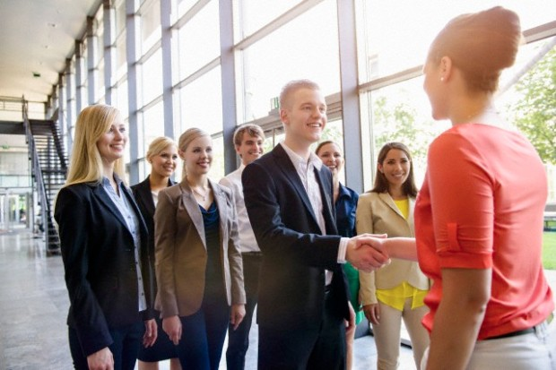 Team of business men and women greeting client in office --- Image by © suedhang/Image Source/Corbis